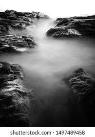 Black & White rocky seascape scene.Beautiful long exposure seascape, rocky beach in black and white.