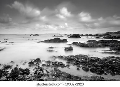 Black White rocky seascape scene.Beautiful long exposure seascape, rocky beach in black and white. soft and grain effect