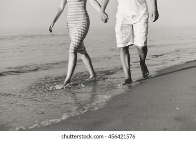 Black and white romantic couple man and woman walking on beach holding hands together, sunny day outdoors background