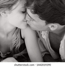 Black and white romantic portrait of beautiful young couple kissing, beach summer holiday heads together, vacation tourists outdoors. Travel holiday coastal leisure recreation, honeymoon lifestyle.