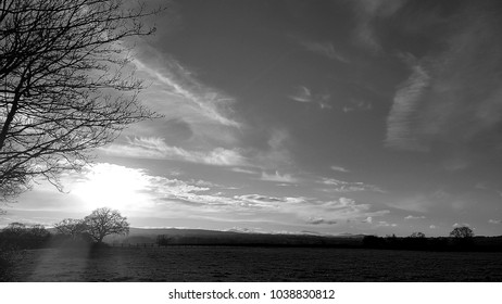 Black and White Rural Landscape with Clouds and Hills in the Distance