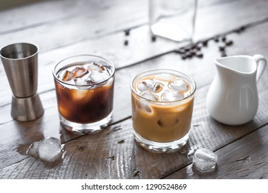 Black and White Russian Cocktails with Vodka, Coffee Liquor and Cream. Homemade iced Alcohol Boozy Black Russian and White Russian drink with coffee beans on wooden background, copy space.