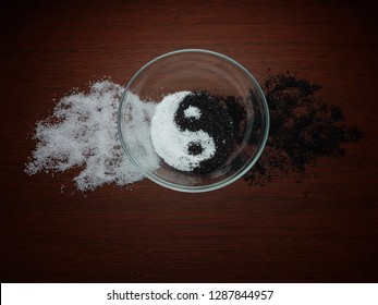 Black and white sand in plate. Abstraction of Yin-Yang, good and evil. Black background.