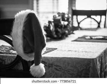 Black and white Santa Hat on chair at dinner table with candles in the background blurred