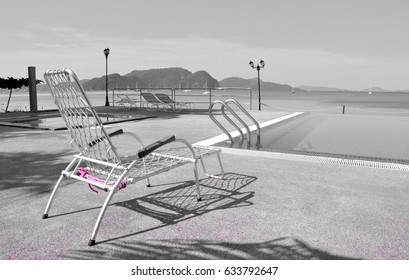 Black and white scene of aluminium sunbed nearby swimming pool and sea
