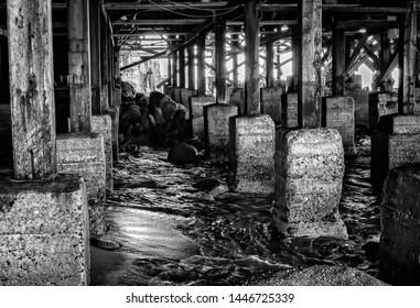 Black and white scene under pier made of wood and cement with ocean water and rusted building.