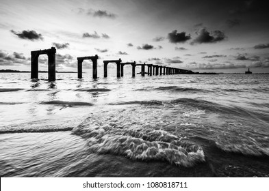 Black and white scenery of the beach with waves and an old jetty
