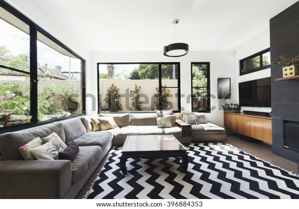 Black and white scheme living room with wood and grey tiling accents and chevron pattern floor rug