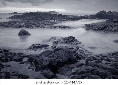 Black and white seascape at dusk. Toned blue. Northern portuguese rocky coast. Long exposure.