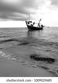 Black and white seascape single boat in the sea with front wave foreground.