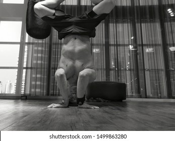 black and white self-portrait picture of man practicing yoga upside down headstand in yoga studio Fitness training Health Club