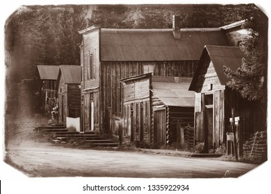 Black and White Sepia Vintage Photo of Old Western Wooden Buildings St. Elmo Gold Mine Ghost Town in Colorado, USA hidden in mountains, with yellow sun glow