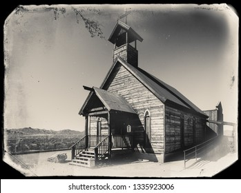 Black and White Sepia Vintage Photo of Old Western Wooden Church in Goldfield Gold Mine Ghost Town in Youngsberg, Arizona, USA surrounded by desert