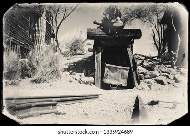 Black and White Sepia Vintage Photo of Goldfield Gold Mine old entrance to gold mine shaft with trolley and rails leading inside, surrounded by cactus and old western building