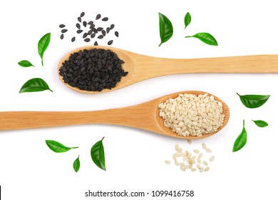 Black and white sesame seeds in a wooden spoon isolated on white background decorated with green leaves. op view