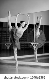 black and white shoot of beautiful dancer ballerina is doing exercises in ballet class