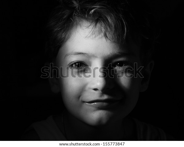 Black and white shot of the boy in the dark, focused light on the head. Very closeup shot, sepia toned. Beautiful sad boy sitting in the dark. Sad little boy monochrome image, copy-space