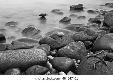 Black and white shot of coastal rocks and dreamy water long exposure