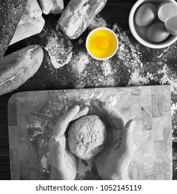 Black white shot with colour popping of egg. Image shows baker kneading organic dough.
