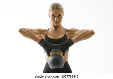 Black and white shot of female bodybuilder in sportswear doing crossfit workout with kettle bell on white background Confident looking forward young athlete with muscular body exercising crossfit.