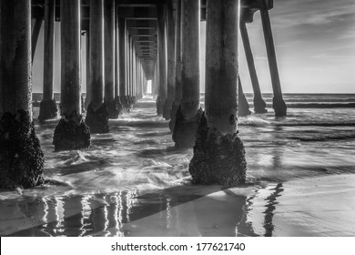 A black and white shot looking out from under the Huntington Beach Pier on a cold winter day.