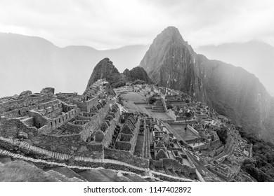 Black and white shot of Machu Picchu during a rainstorm