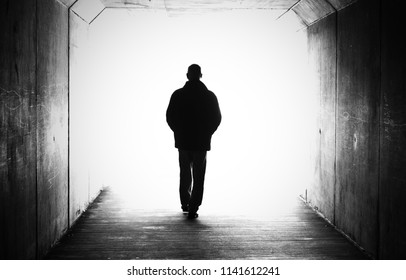 Black and white shot of a male person figure in a tunnel heading towards a bright light. Concept of near death experience, dying, afterlife, moving on, transition, heaven. walking towards the light.