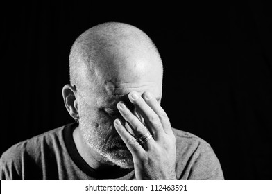 Black and white shot of a middle aged bald man with facial hair holding his head in his hands with a black background