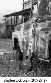 black and white shot of an old acoustic guitar leaning up against an old rusted out truck parked on the grass with an old shack in the background in Clarksdale Mississippi