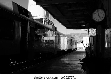 A black and white shot of an old train waiting at the station.