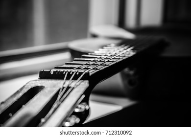 Black and white shot of scratched fretboard of ol acoustic guitar in close-up.