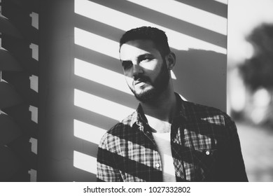 d369d7811b a black and white shot of a standing man looking out of the window the sun