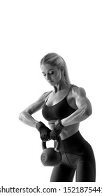 Black and white shot at studio Strong and powerful concept vertical photo with copy free space on top Attractive sweaty muscular woman with pumping kettle bell over white background