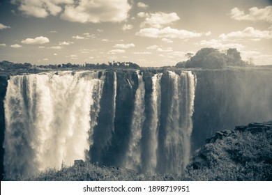 Black and white shot of Victoria Falls with lots of water and small cumulous clouds