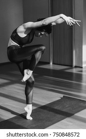 black and white shot of young female dancer training in studio
