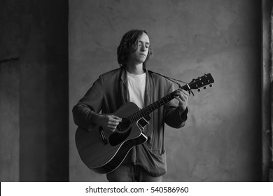 Black and white shot of a young musician playing his acoustic guitar.
