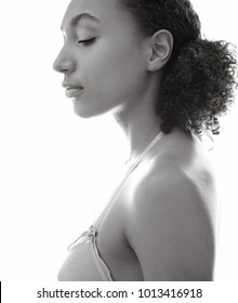 Black and white side portrait of beautiful young african american woman wearing bra, against light background. Black female beauty, healthy well being, feminine purity sensual innocence, lifestyle.