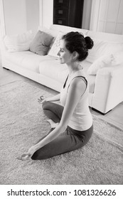 Black and white side view of beautiful woman practicing yoga at home in meditation position, living room indoors. Healthy peaceful sport activities home interior. Leisure recreation lifestyle wellness