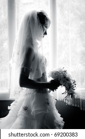 black and white silhouette of the bride weared in dress and veil with a bouquet
