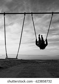 Black and white silhouette of girl on a swing
