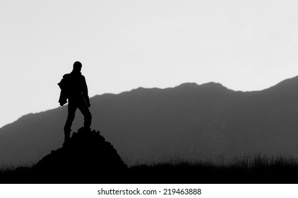 Black and white silhouette of hiker on the top of the hill