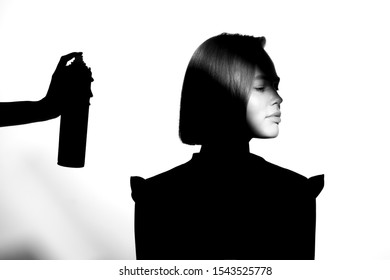 Black and white silhouette portrait with shadow and spot of light. The girl uses hairspray. Hair cosmetic concept.