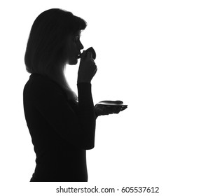 Black and white silhouette portrait of young woman drinking hot coffee on isolated background