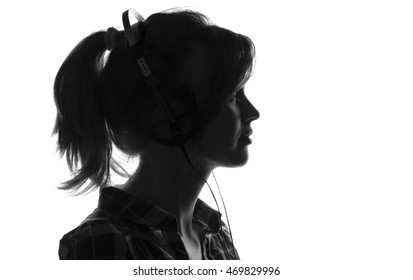Black and white silhouette woman head in headphones, profile of a beautiful young girl listening to music