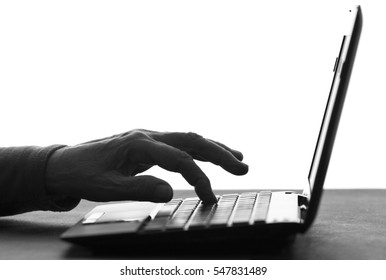 black and white silhouette of wrinkled hands of an elderly woman typing on the keyboard