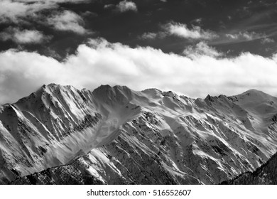 Black and white snow winter mountains and cloud sky in sun evening. Caucasus Mountains. Svaneti region of Georgia.