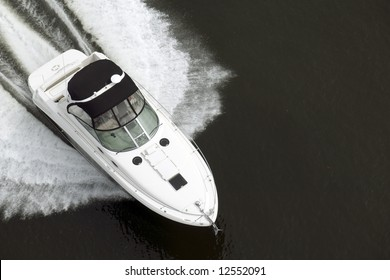 A black and white speedboat shot from above while traveling fast.