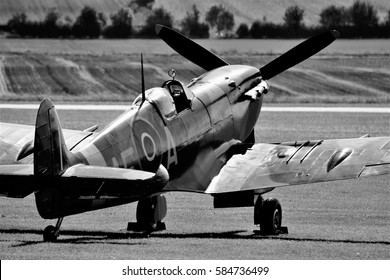 Black and white Spitfire aircraft on the ground