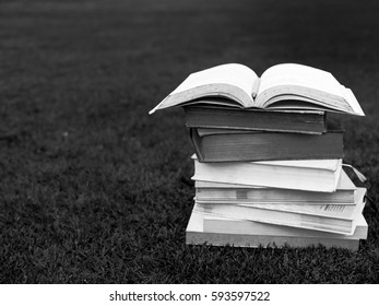 black and white of stack of books on table in garden with top one opened