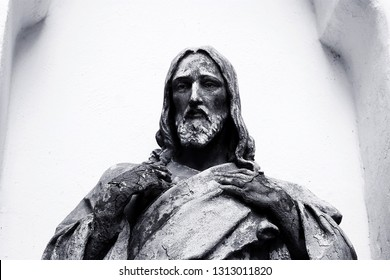 black and white statue of jesus with cracks in his arms he looks into the distance and presses his arms to his chest